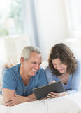 Couple Using Digital Tablet While Relaxing In Bed Royalty Free Stock Photo