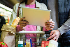 Couple using digital tablet while shopping Royalty Free Stock Images