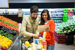 Couple using digital tablet while shopping Stock Photos