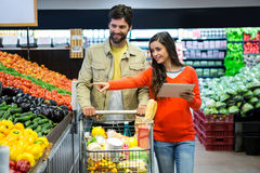 Couple using digital tablet while shopping Stock Photo