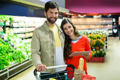 Couple using digital tablet while shopping Stock Image