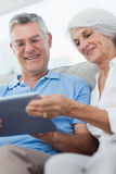 Couple using a digital tablet sitting on the couch Stock Photography