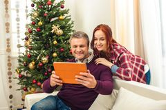 Couple with digital tablet at christmastime. Couple using digital tablet while sitting together on sofa at christmastime royalty free stock image