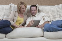 Couple Using Digital Tablet On Sofa Royalty Free Stock Photography