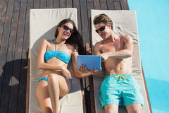 Couple using digital tablet on sun loungers by swimming pool Stock Image