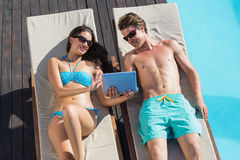 Couple using digital tablet on sun loungers by swimming pool Stock Photography