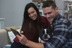 Couple using digital tablet with their pet dog in living room stock photos