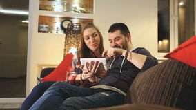 Couple using digital tablet touchscreen ipad watching movies, smiling and having fun. Couple using digital tablet touchscreen ipad, watching movies stock footage
