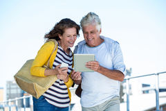 Couple using digital tablet on walkway Royalty Free Stock Photography