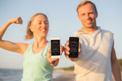 Couple using fitness app on their mobile phones. Couple using fitness app on their smart- phones Stock Image