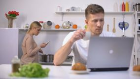 Couple using gadgets in kitchen, ignoring live communication, addiction concept. Stock footage stock video footage