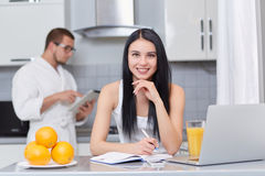 Couple using gadgets and studying at kitchen. Royalty Free Stock Photo