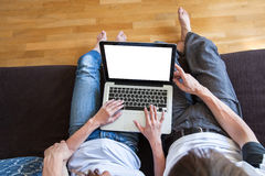 Couple using internet on laptop at home. Young couple using internet on laptop with empty blank screen at home, top view, buy or rent online concept Royalty Free Stock Image