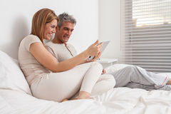 Couple using the ipad in the bed stock images