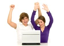 Couple using laptop. Couple with arms raised using laptop Royalty Free Stock Photo