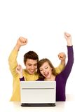 Couple using laptop. Couple with arms raised using laptop Stock Photography