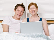 Couple using laptop in bed Stock Images