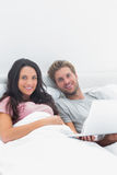 Couple using a laptop in bed Royalty Free Stock Image