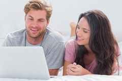 Couple using laptop in bed Stock Photos