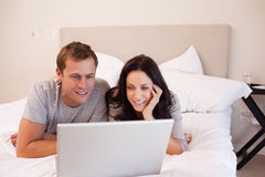 Couple using laptop on the bed together Royalty Free Stock Photo