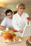 Couple using laptop at breakfast Royalty Free Stock Photos