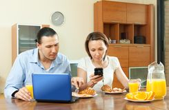 Couple using laptop during breakfast at home Stock Photography