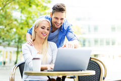 Couple using laptop at cafe Royalty Free Stock Photos
