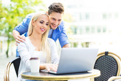 Couple using laptop at cafe Royalty Free Stock Images