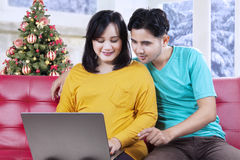 Couple using laptop in christmas day Stock Photo