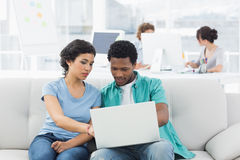 Couple using laptop with colleagues at creative office Stock Image