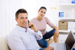 Couple using laptop computer. Young couple using laptop computer at home, sitting on couch. Man talking on mobile phone. Selective focus on man Stock Photo