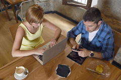 Couple using laptop computer and mobile phone networking ignoring each other Royalty Free Stock Photo