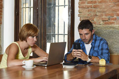 Couple using laptop computer and mobile phone networking ignoring each other Royalty Free Stock Image