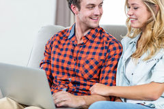 Couple using laptop on the couch Royalty Free Stock Image