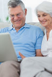 Couple using a laptop on the couch royalty free stock images