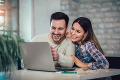 Couple Using Laptop On Desk At Home. Young Couple Using Laptop On Desk At Home stock images