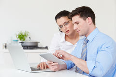 Couple Using Laptop And Digital Tablet At Home Royalty Free Stock Photos
