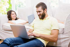 Couple using laptop and digital tablet in living room Royalty Free Stock Photos