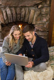 Couple using laptop in front of lit fireplace Royalty Free Stock Image