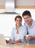 Couple using a laptop while having coffee Royalty Free Stock Images