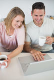 Couple using laptop while holding coffee cups Royalty Free Stock Photo