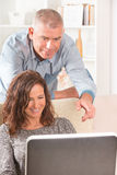Couple using laptop at home Stock Image