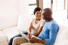 Couple using laptop home Stock Images