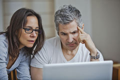 Couple using a laptop at home Stock Images