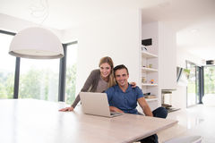 Couple using laptop at home Stock Images