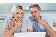 Couple using laptop in the kitchen Royalty Free Stock Photos