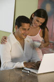 Couple Using Laptop on The Kitchen Counter Stock Photo
