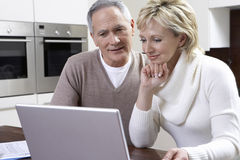 Couple Using Laptop At Kitchen Table. Happy middle aged couple using laptop at kitchen table Stock Images