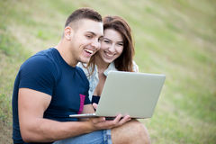Couple using laptop on lawn Stock Image
