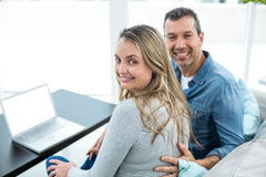 Couple using laptop in living room Stock Image
